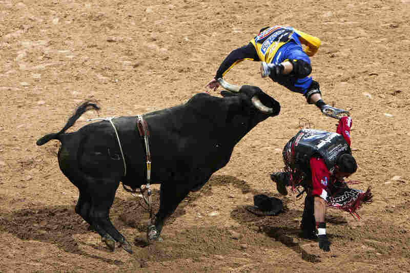 World Champion Guilherme Marchi of Brazil (right) is thrown from his ride, as bullfighter Joe Baumgartner (left) is tossed by Jumpin Jack Flash during the 2006 Professional Bull Riders World Finals in Las Vegas.