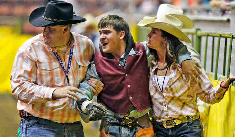 James Carter of Fort Scott Community College (center) is helped out of the rodeo arena after suffering an injury, concluding a bareback ride at the 2008 College National Finals Rodeo championship round in Casper, Wyo.