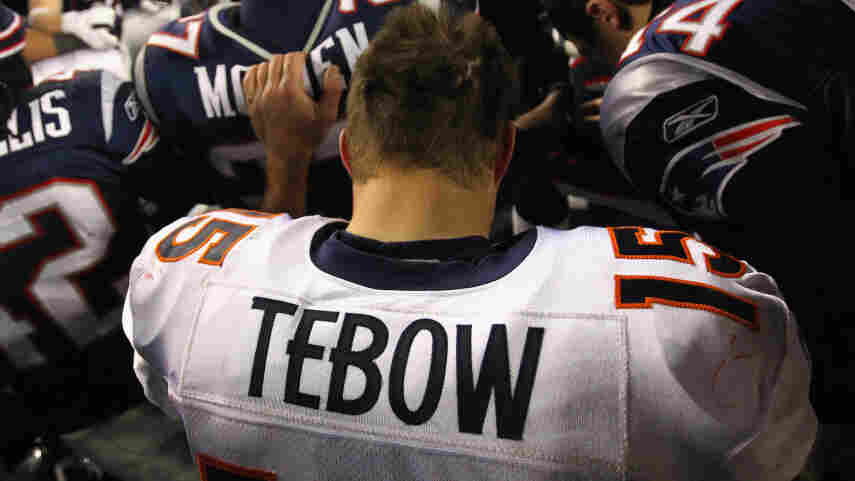 Tim Tebow of the Denver Broncos kneels and prays with teammates and members of the New England Patriots after the Patriots won 45-10 during their AFC Divisional Playoff Game at Gillette Stadium on January 14, 2012.