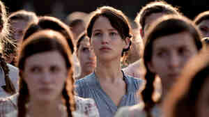 In The Hunger Games, Katniss Everdeen (Jennifer Lawrence) volunteers to take her little sister's place in a killing ritual televised to the masses.