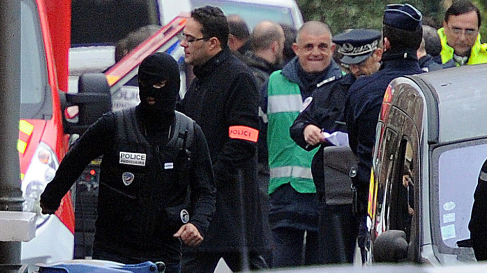 French police officers at the scene of the siege today in Toulouse, where a suspect in recent killings is said to be holed up in an apartment.