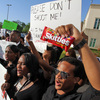 "Brandon Northington (right) a FAMU law student chants, ""Do I look suspicious?"" while holding a bag of Skittles during a rally Monday at the Seminole County Courthouse in Sanford, Fla. Trayvon Martin was holding the candy when he was shot and killed."