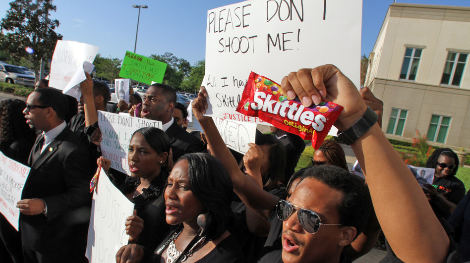 "Brandon Northington (right) a FAMU law student chants, ""Do I look suspicious?"" while holding a bag of Skittles during a rally Monday at the Seminole County Courthouse in Sanford, Fla. Trayvon Martin was holding the candy when he was shot and killed. (MCT /Landov)"