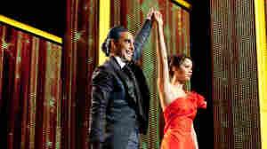 Are You Not Entertained? TV host Caesar Flickerman (Stanley Tucci) takes the celebrity interview to new lows when chatting up the young combatants in the to-the-death Hunger Games — including Katniss Everdeen (Jennifer Lawrence).
