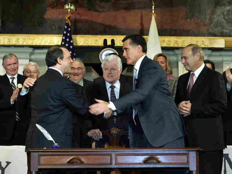 Then-Massachusetts Gov. Mitt Romney shakes hands with Massachusetts Health and Human Services Secretary Timothy Murphy after signing a landmark state health care law on April 12, 2006, in Boston. Sen. Edward Kennedy, D-Mass., stands at center.