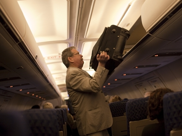 A passenger puts his luggage in the overhead bin on an American Airlines flight out of John F. Kennedy Airport in Jamaica, New York.