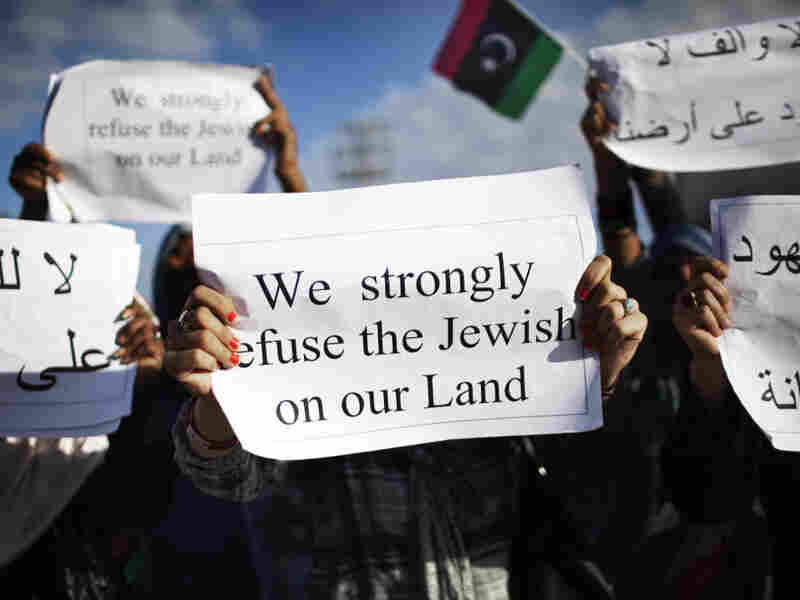 Libyans hold signs during a demonstration against the presence of Jews in Libya and the reopening of the Dar Bishi Synagogue in Tripoli on Oct. 7, 2011.
