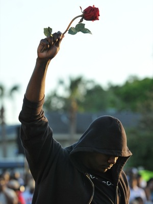 Wearing a hoodie and holding a rose, James Gilchrist of Orlando, Fla., attends a rally for Trayvon Martin on Thursday in Sanford, Fla.