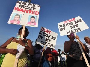 Protesters demonstrate at a rally for slain teenager Trayvon Martin on March 22, 2012 in Sanford, Fla.