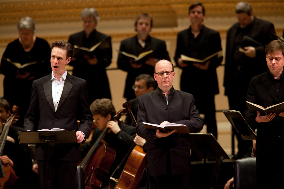 "Tenor Ian Bostridge (left) sings the role of the evangelist, a kind of ""reporter on the scene"" telling the story of Jesus' arrest, trial, and crucifixion. He's joined by Bass-Baritone Neal Davies (center, as Jesus) and Bass-Baritone Hanno Muller-Brachmann.  (NPR)"