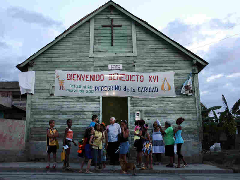 Parishioners stand outside a Catholic church in a poor Santiago suburb on Saturday in Cuba. Pope Benedict XVI is in Mexico but will head to Cuba next for a three-day visit.