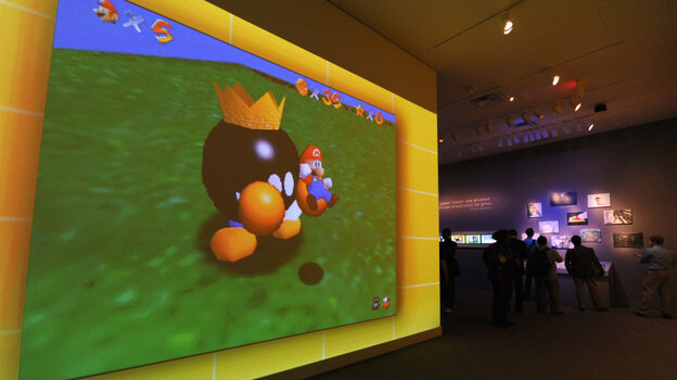 "A large video screen shows a scene from Super Mario Bros. at the exhibition ""The Art of Video Games."""