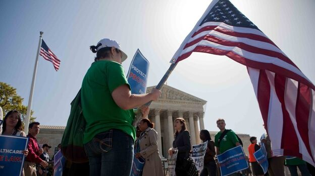 Demonstrators in support of President Obama's health care overhaul march outside the U.S. Supreme Court on Monday.  (NPR)