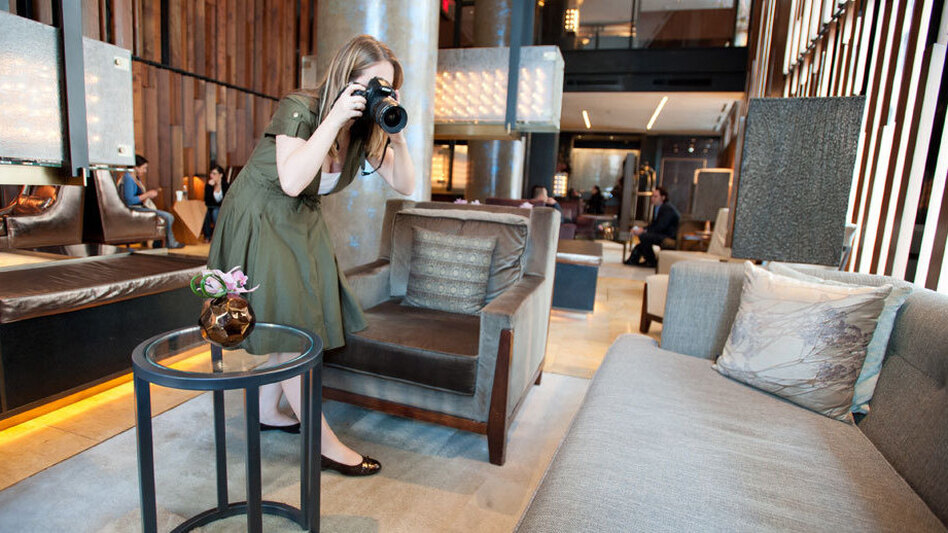 Kelsey Blodget of Oyster.com photographs the lobby of New York's Trump SoHo hotel. The website relies on tech-savvy workers to create online reviews and track hotel bookings.
