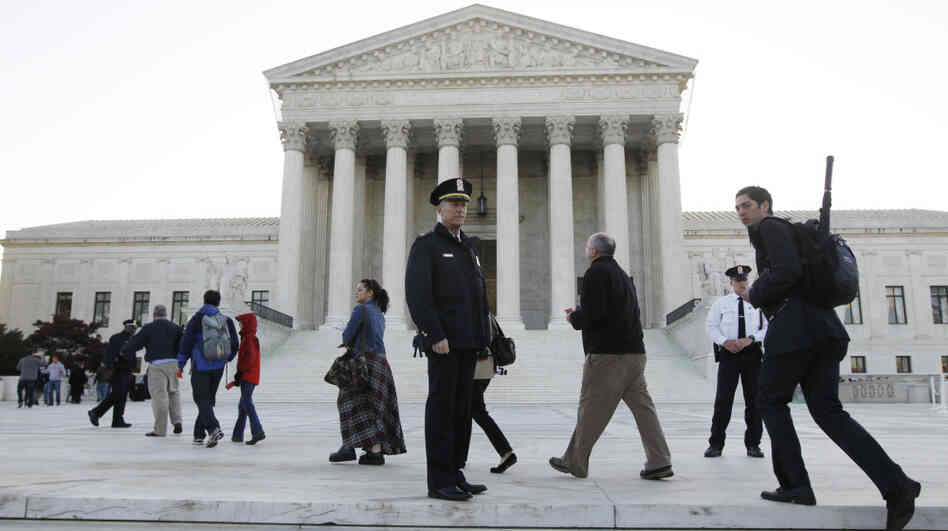 Members of the public line up Monday morning as the Supreme Court begins three days of arguments on the health care overhaul law signed by President Obama in Washington.