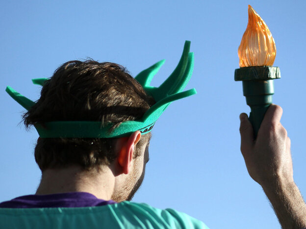 An activist dressed as the Statue of Liberty participates in a protest on the second day of oral arguments over President Obama's health care law on Tuesday.