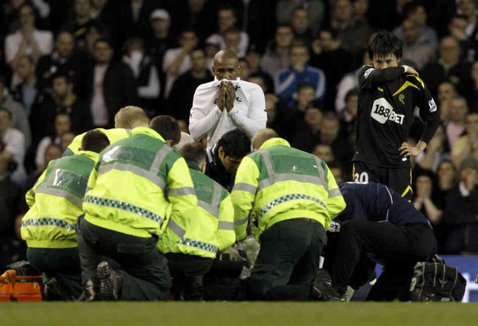 Bolton Wanderers' Fabrice Muamba is obscured by medical staff trying to resuscitate him after collapsing. His teammate Ryo Miyaichi, right, and Tottenham Hotspur's Je