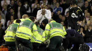 Bolton Wanderers' Fabrice Muamba is obscured by medical staff trying to resuscitate him after collapsing. His teammate Ryo Miyaichi, right, and Tottenham Hotspur's Jermain Defoe, cent