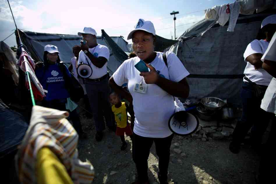 A GHESKIO worker walks through a tent camp in Port-au-Prince with a megaphone, warning people about the danger of cholera and the need for sanitation and clean water.