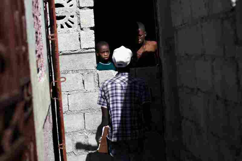 A GHESKIO worker goes door to door in Cite de Dieu. As part of the planned vaccination campaign, an army of health workers has gone out to inform Haitians about cholera and sign them up to get the vaccine.