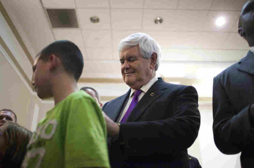 Republican presidential candidate, former House Speaker Newt Gingrich, right, signs a shirt after speaking in Hockessin, Del. on Monday.