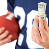 Football player holding football and cash
