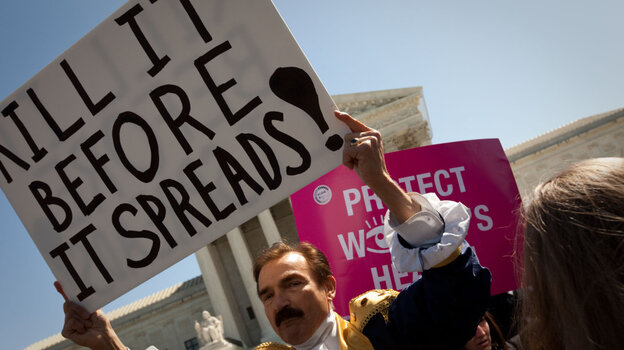 Opponents and supporters of President Obama's health care overhaul rallied outside the Supreme Court on Tuesday. Bob Mason shows support for the Tea Party by dressing in costume as one of the Founding Fathers.