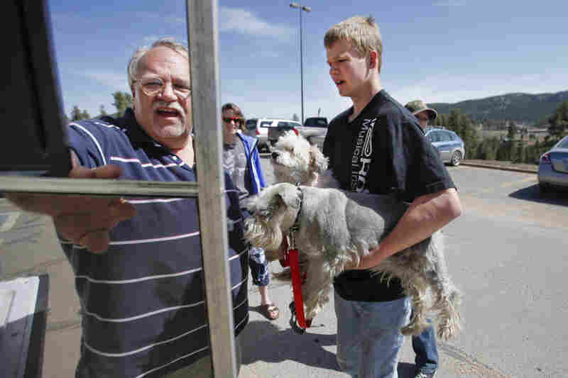 Bob Gardner (left) and his grandson, Zach Gardner, 16, load two of their dogs in a car at Conifer High School where they spent the night after being evacuated on Tuesday.