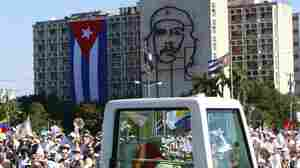 Back dropped by an image of Cuba's revolutionary hero Ernesto 'Che' Guevara, Pope Benedict XVI waves to faithful from his popemobile as arrives at Revolution Square for a Mass in Havana, Cuba on Wednesday.