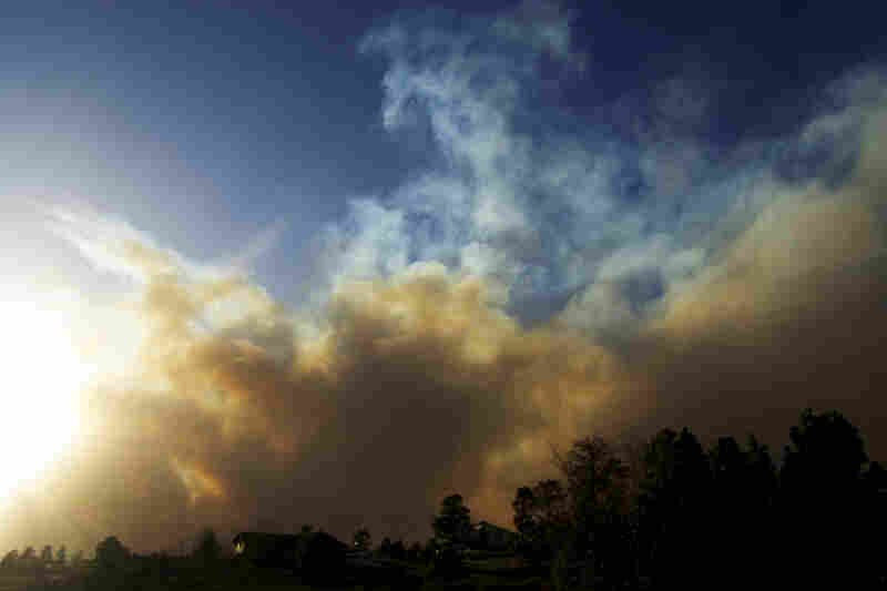 A plume of smoke rises over the top of a wildfire burning out of control near Conifer, Colo., on Monday. High winds fanned the fire and kept aircraft from being used to knock it down.