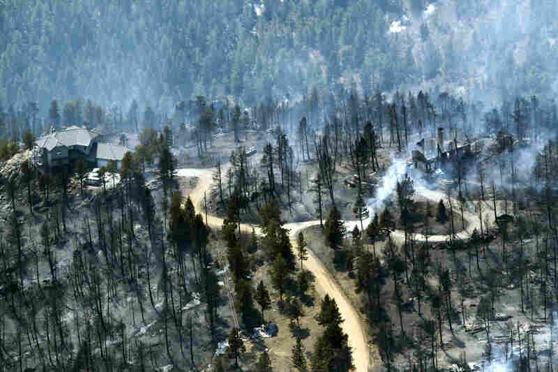 A home at left stands untouched while the one at right smolders after burning in the Lower North Fork Wildfire in the foothills southwest of Denver on Tuesday.