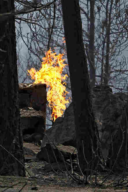 Flames rise from a propane tank near a home destroyed by a wildfire burning in Conifer.