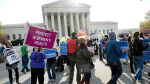 Activists gather in front of the U.S. Supreme Court on Wednesday as the court hears a third day of arguments on President Obama's health care law.