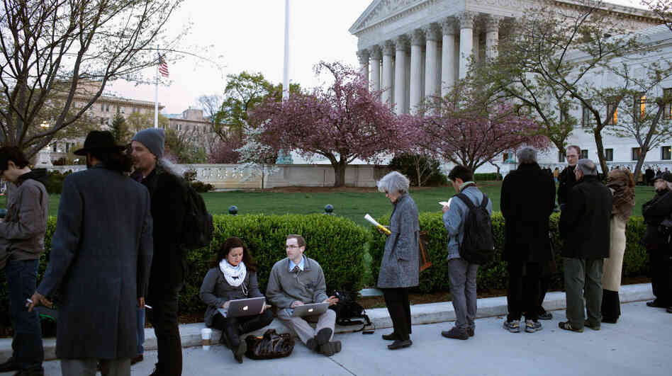 People wait for tickets to attend the last day of arguments over the Affordable Care Act at the Supreme Court.