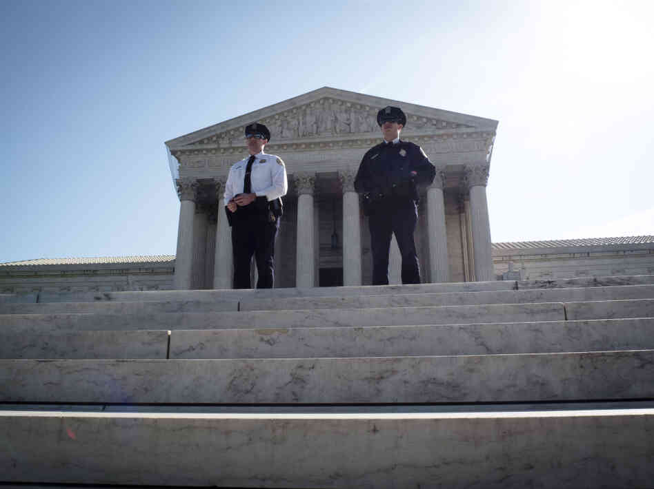 Two policemen guard outside the US Supreme Court on the third day of oral arguements over the constitutionality of the Patient Protection and Affordable Care Act on March 28, 2012 in Washington, DC. The 26 states challenging the law argue that the Act must be completely repealed.