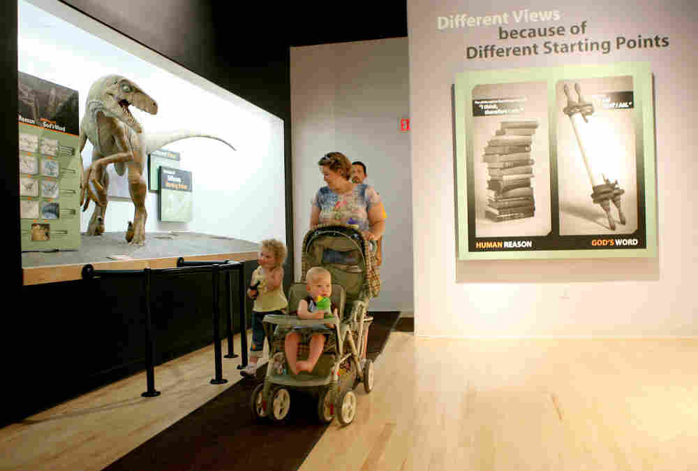 Elizabeth Burrows of LaGrange, Kentucky, walks with her children, as they tour the Creation Museum in Petersburg, Ke