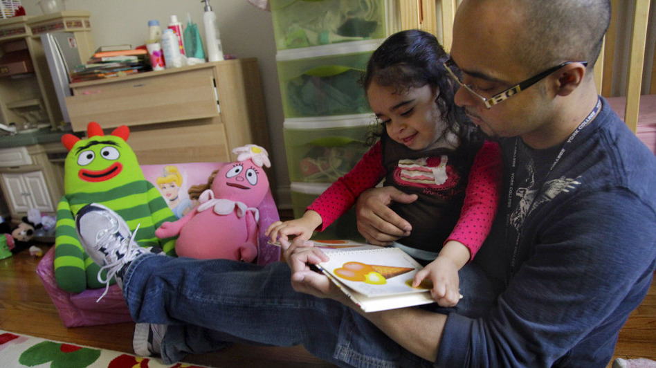 Christopher Astacio reads with his daughter Cristina, 2, recently diagnosed with a mild form of autism, in her New York bedroom on Wednesday.  (AP)