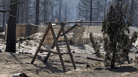 The ruins of a home destroyed by a wildfire are framed by a child's swing set near Conifer, Colo., on Wednesday, March 28, 2012.