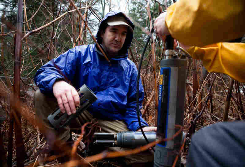 Andrew Gavin (left) of the Susquehanna River Basin Commission checks the readings from a device set up to monitor water quality at Gray's Run stream, near Williamsport, Pa.