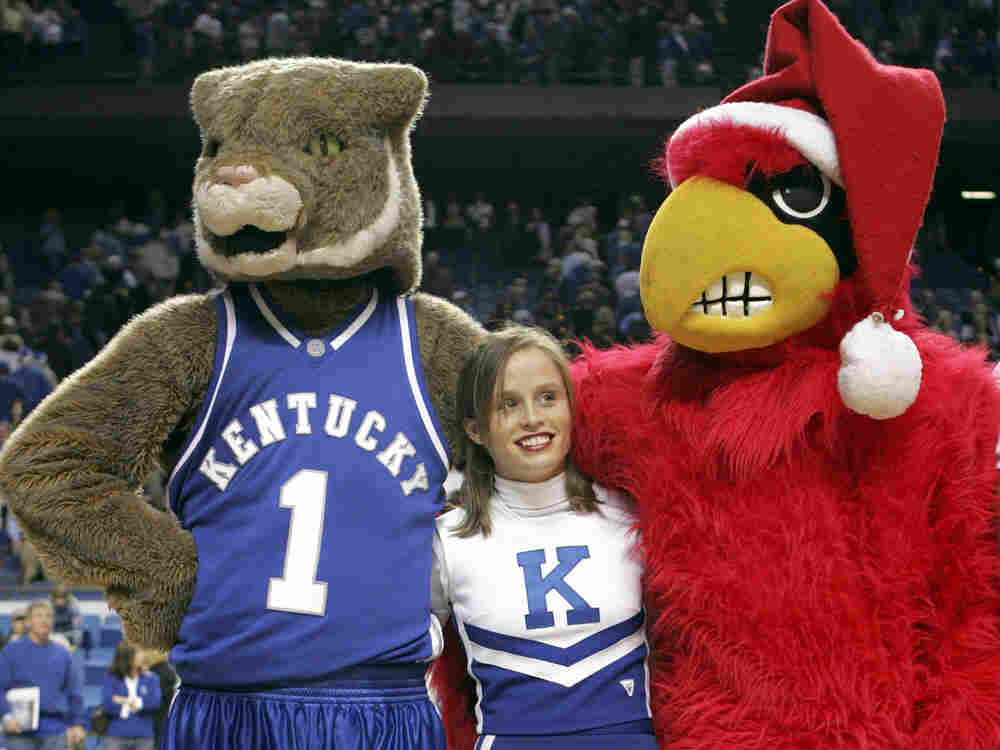 """A cheerleader for the Kentucky Wildcats stands between the mascots for Kentucky and the Louisville Cardinals as they sing """"My old Kentucky Home"""" after the game at Rupp Arena on December 17, 2005 in Lexington, Kentucky. In our second hour, die hard fans talk about long standing team rivalries in their town."""