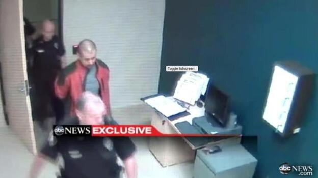 George Zimmerman, in the red jacket, as he was led through a police station in Sanford, Fla., after the Feb. 26 shooting death of Trayvon Martin. (ABC News)