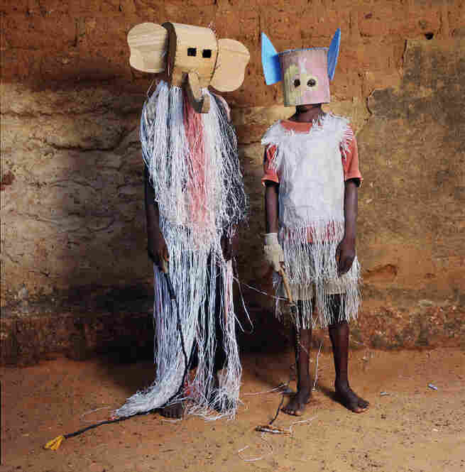 """An elephant and a bat pose at the Dodo Masquerade in Burkina Faso, an event where children don masks, sing and dance under a full moon."""