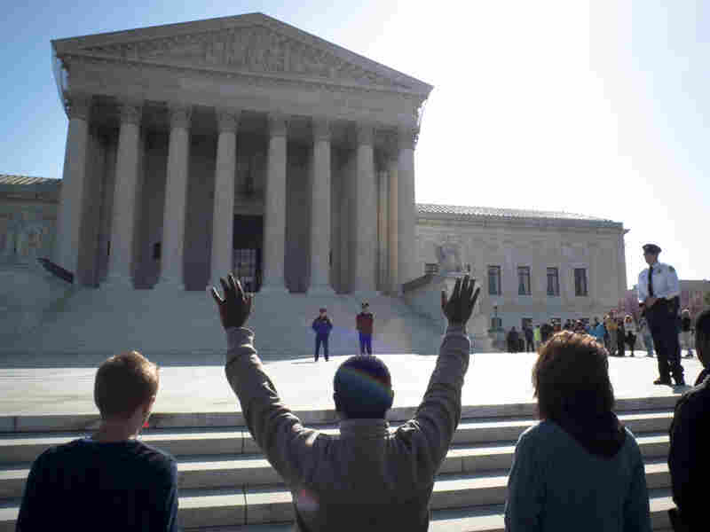 Anti-abortion protesters pray outside the U.S. Supreme Court on the third day of oral arguements over the constitutionality of the Patie