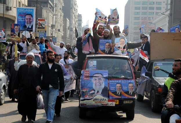 Supporters of an Egyptian Islamist candidate hold his posters as they drive through C