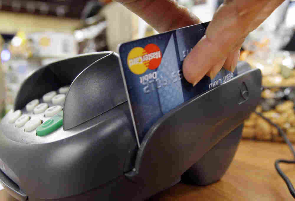 A customer swipes a MasterCard debit card through a machine while checking-out at a shop in Seattle.