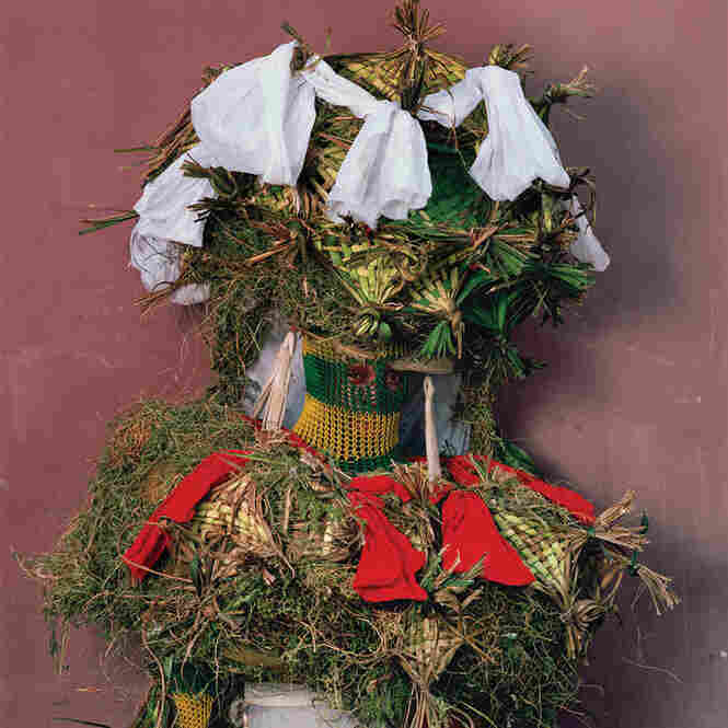 """Other spirits represent nature of esteemed ancestors who guide, judge, or entertain the living. They're portrayed with forest greenery and netlike facribs ... during Christmastime in urban Calabar [Nigeria]."""