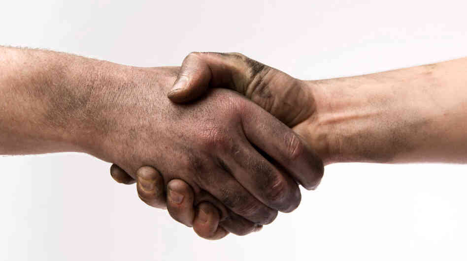 Two people with dirty hands shaking hands.