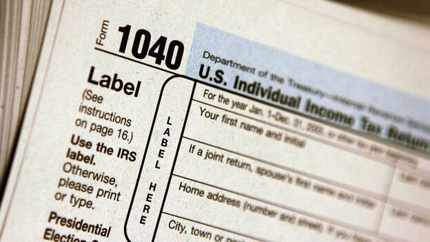 A pile of IRS Form 1040 tax documents is seen in this file photo. Personal finance experts recommend keeping most records for three years after they're used in a tax return.