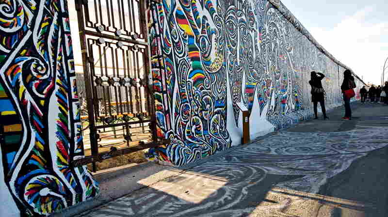 "Tourists take photographs of the murals painted onto the section of the Berlin Wall known as the ""East Side Gallery"" in central Berlin, on Nov. 7, 2009."