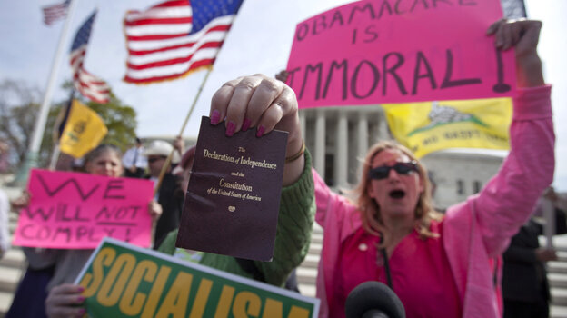 Protesters chant and hold a copy of the Declaration of Independence and the Constitution in front of Supreme Court in Washington as the court concluded three days of hearing arguments on the constitutionality of President Barack Obama's health care